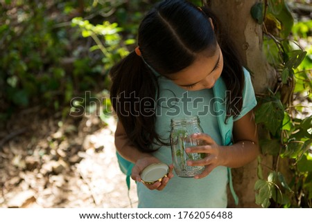 little girl with backpack looking at jar with plant on a sunny day in the forest stock photo © wavebreak_media