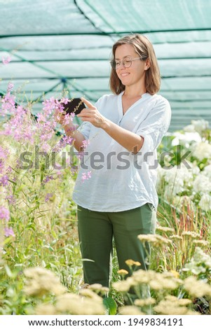 Woman gardener standing over flowers plants in greenhouse holding plants stock photo © deandrobot