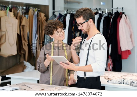 Young clothing designers discussing details of new digital sketches Stock photo © pressmaster