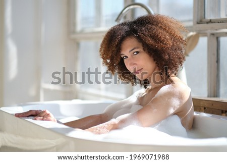 Beautiful african american woman bathing in a tub full of foam Stock photo © boggy