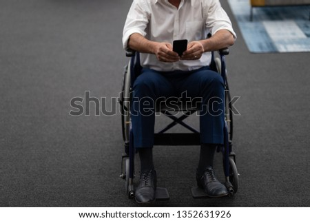 Low section of mature Caucasian disabled businessman using mobile phone while sitting on wheelchair  Stock photo © wavebreak_media