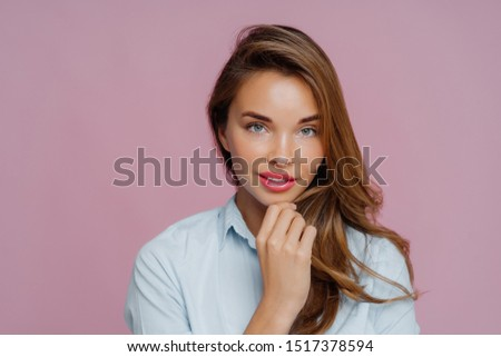 Portrait of lovely long haired woman touches chin, has blue eyes, looks confidently at camera, wears Stock photo © vkstudio