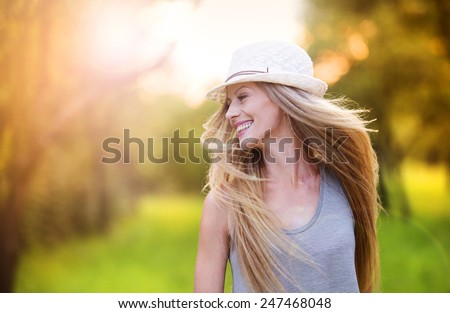 Attractive young woman enjoying her time outside in park with sunset in background. Stock photo © ElenaBatkova