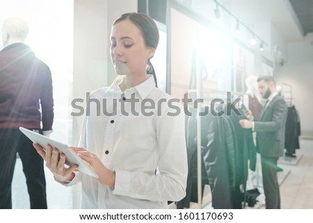 Young elegant shop assistant scrolling in touchpad on background of client Stock photo © pressmaster