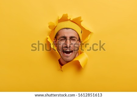 Isolated shot of unhappy desperate man with stubble keeps hands  Stock photo © vkstudio