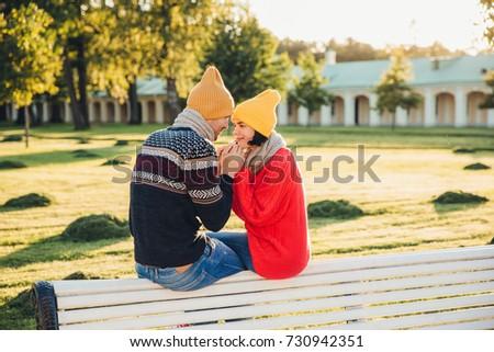 Romantic couple sit on bench, enjoy sunny day, keep hands togeth Stock photo © vkstudio