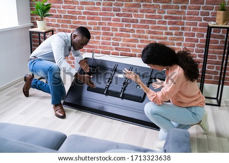 Couple Looking At Fallen Television Stock photo © AndreyPopov