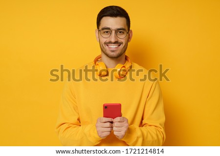 Image of young handsome man wearing sweater holding his eyeglasses Stock photo © deandrobot