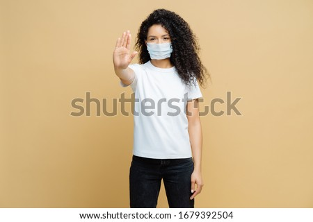 Say no to spreading disease. Serious looking Afro American woman makes stop gesture, wears medical m Stock photo © vkstudio