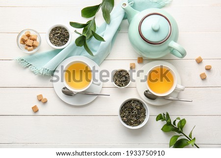 Green tea with natural flavors and a teapot. Top view on white background Stock photo © butenkow