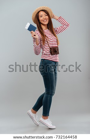 Image of happy brunette asian woman holding passport and travel  Stock photo © deandrobot