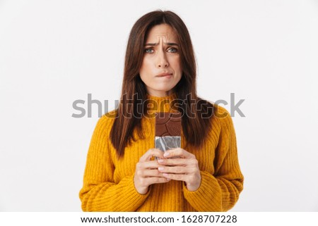 Image of beautiful adult woman hesitating while holding chocolat Stock photo © deandrobot