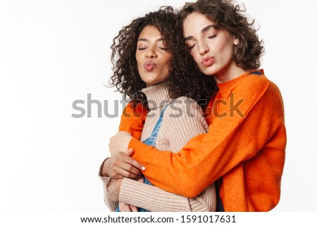 Portrait of cute multinational women making kiss lips and hugging Stock photo © deandrobot