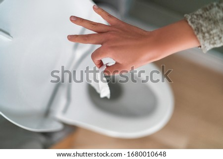 Flushing down disinfectant wipes as toilet paper shortage alternative during panic buying coronaviru Stock photo © Maridav