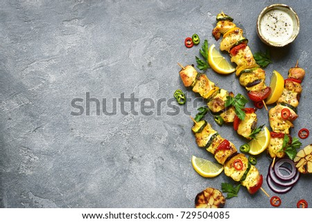 Grilled pork and chicken kebab with paprika on stone chopping board with salt, pepper and tomatoes o Stock photo © DenisMArt