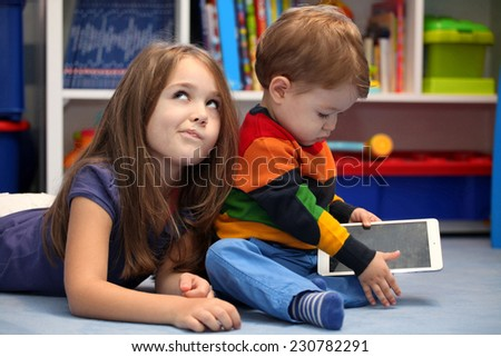 Disappointing girl with her little brother using a tablet comput Stock photo © vladacanon