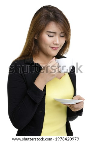 smiling woman in black dress standing and holding cup with coffe over gray background stock photo © deandrobot