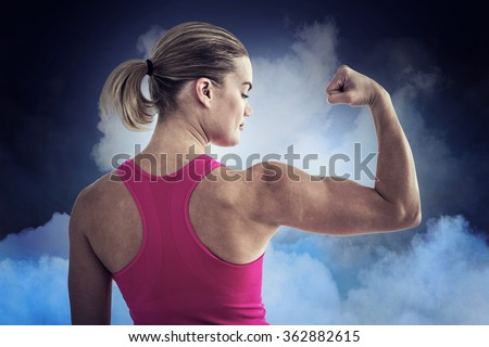 Foto stock: Fit woman flexing muscles against digitally generated background