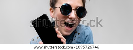 Young brunette girl in round glasses. Hairs are gathered in a bun. Girl with a black phone. Stock photo © Traimak