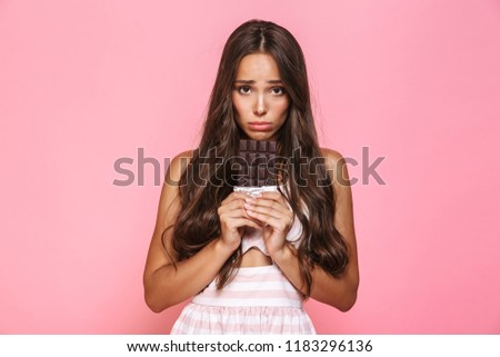 photo of frustrated woman 20s wearing dress holding chocolate ba stock photo © deandrobot