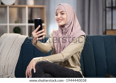 Photo of cheerful arabian woman wearing headscarf using mobile p Stock photo © deandrobot
