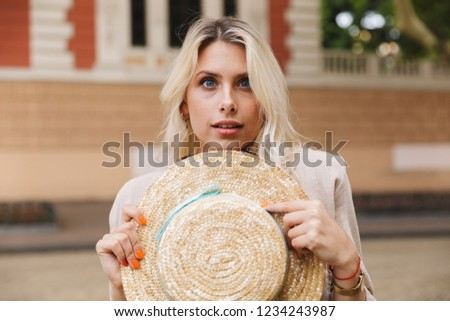 Image of cute girl 20s holding straw hat, while walking through  Stock photo © deandrobot