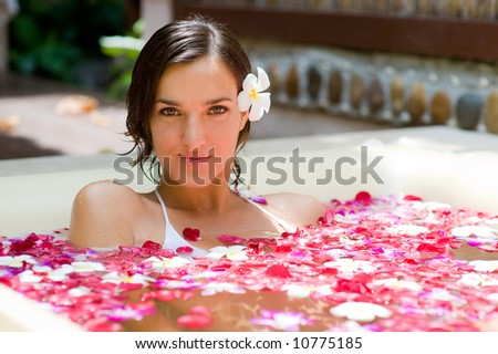 Attractive Young woman in bath with petals of tropical flowers and aroma oils. Spa treatments for sk Stock photo © galitskaya
