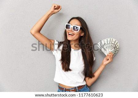Photo of joyous woman with long dark hair in sunglasses showing  Stock photo © deandrobot