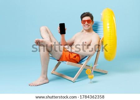 Summer lifestyle portrait of man sitting on the orange inflatable sofa on the beach of tropical isla Stock photo © galitskaya