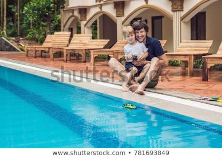 Vader zoon spelen afstandsbediening boot zwembad familie Stockfoto © galitskaya