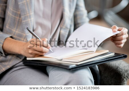 young school teacher with pen correcting mistakes or putting mark in copybook stock photo © pressmaster