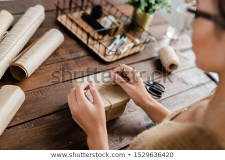 hands of young female making knot on top of giftbox while packing gifts stock photo © pressmaster