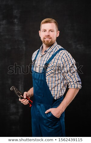 Happy young bearded mechanic in coveralls and shirt using handtool while working Stock photo © pressmaster