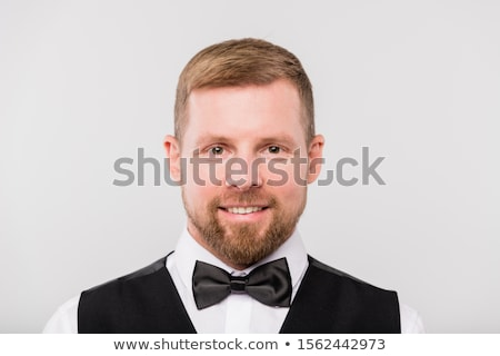 Young smiling bearded waiter in black waistcoat and bowtie looking at you Stock photo © pressmaster