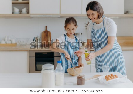 Brunette mother adds oil in dough, little daughter helps to make pastry, whisks ingredients, pose to Stock photo © vkstudio