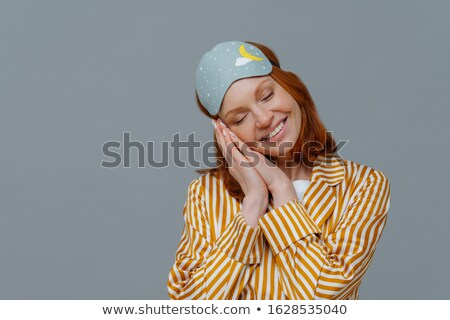 Deep sleep and pleasure. Pretty freckled woman tilts head, smiles broadly, shows white teeth, wears  Stock photo © vkstudio