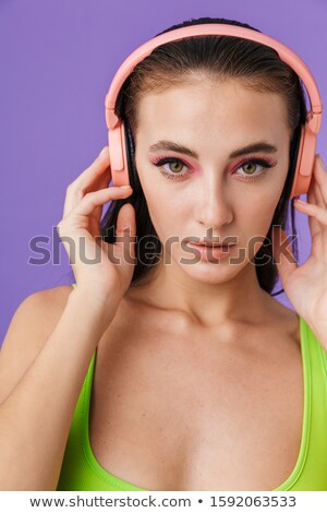 photo of nice fashion woman using headphones and looking at camera stock photo © deandrobot