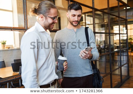 Image of pleased businessman talking on cellphone while standing Stock photo © deandrobot