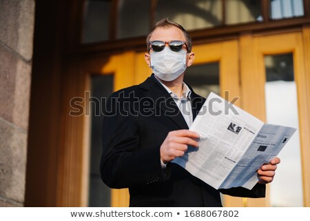 Caucasian man in sunglasses, medical mask and formal black suit, stands near building outdoor, holds Stock photo © vkstudio