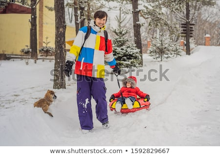 Dad and son have fun on tubing in the winter. Winter fun for the whole family Stock photo © galitskaya