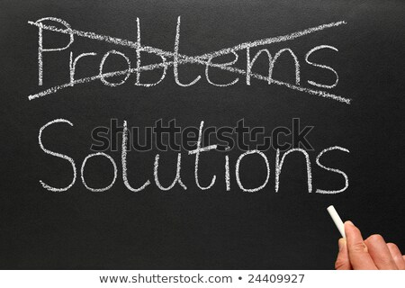 Crossing out problems and writing solutions on a blackboard. Stock photo © latent
