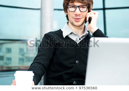 Stock photo: Friendly executive sitting in front of laptop