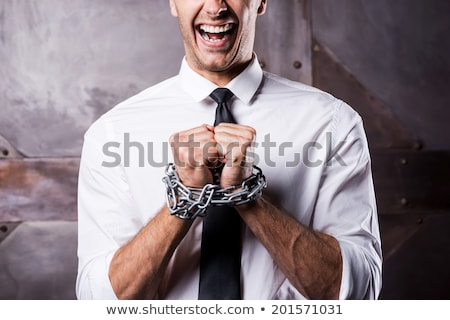 man with hands tied up with chains stock photo © andreykr