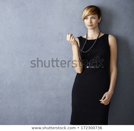 Portrait of a serious beautiful woman in black dress on gray background Stock photo © deandrobot