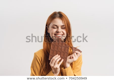 portrait of a young woman biting chocolate isolated on white stock photo © id7100