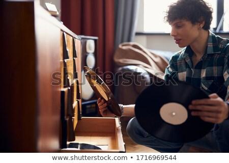 Moço olhando vinil coleção casa sala de estar Foto stock © wavebreak_media
