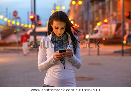Beautiful woman use her phone in the city at night. Stock photo © nenetus