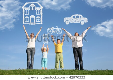 Сток-фото: Family Of Four On Grass With Hands Up And Dream Collage