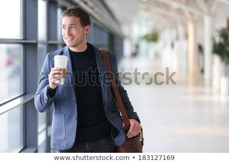 Smiling businessman holding jacket on the shoulder  Stock photo © deandrobot