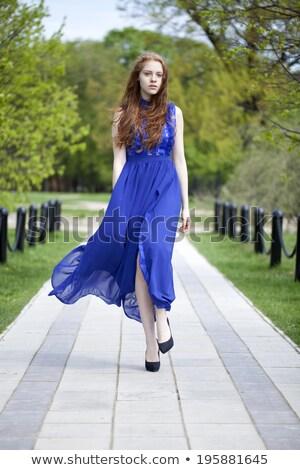 Young beautiful woman blue dress walking path in park. Stock photo © artfotodima
